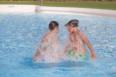 Dos muchachos adolescentes que juegan junto en la piscina Fotos de archivo