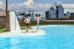 Dos muchachos adolescentes saltan en la piscina Foto de archivo libre de regalías