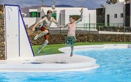 Dos muchachos adolescentes saltan en la piscina Imagen de archivo