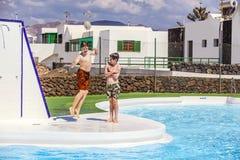 Dos muchachos adolescentes se divierten en la piscina Foto de archivo libre de regalías