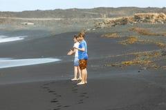 Dos muchachos adolescentes se divierten en una playa volcánica negra Fotos de archivo libres de regalías