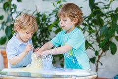 Dos muchachos adorables que hacen el experimento con las burbujas coloridas Imágenes de archivo libres de regalías