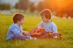 Dos muchachos adorables, sentándose en la hierba, tocando la guitarra Fotos de archivo