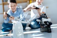 Dos muchachos alegres que luchan con sus robots Foto de archivo