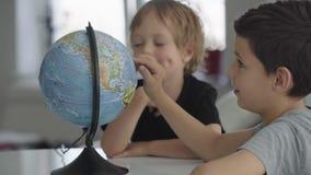 Dos muchachos caucásicos hacen girar un globo y un sueño sobre viaje metrajes