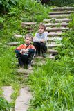 Dos muchachos caucásicos que se sientan en una escalera de piedra al aire libre en verano fotos de archivo