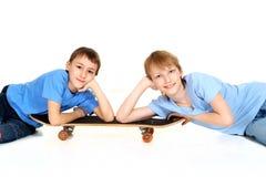 Dos muchachos colocan en el patín Imagenes de archivo