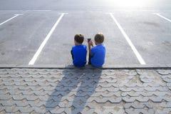 Dos muchachos con el teléfono móvil que se sienta en un estacionamiento vacío Niñez, educación, aprendiendo, tecnología, concepto Foto de archivo