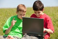Dos muchachos con la computadora portátil en el prado Imagen de archivo libre de regalías