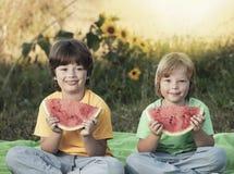 Dos muchachos con la fruta en parque Ni?o feliz que come la sand?a en el jard?n imagen de archivo
