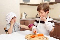 Dos muchachos con la zanahoria y la cebolla Fotografía de archivo