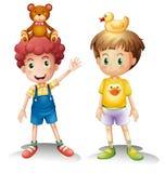 Dos muchachos con sus juguetes sobre sus cabezas Imagen de archivo libre de regalías