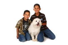 Dos muchachos con un perro blanco Foto de archivo libre de regalías