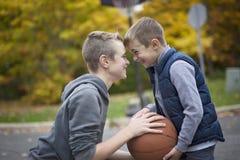 Dos muchachos con una bola de la cesta Imagen de archivo libre de regalías