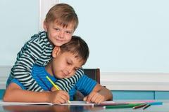 Dos muchachos de drenaje en el escritorio Imagenes de archivo