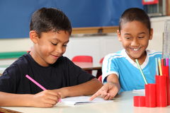 Dos muchachos de escuela felices que comparten el aprendizaje en clase Foto de archivo libre de regalías