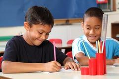Dos muchachos de escuela que disfrutan de su aprendizaje en clase Fotos de archivo