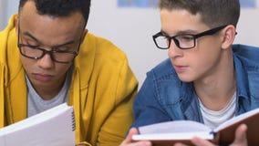 Dos muchachos de escuela secundaria que hacen la preparación para la clase siguiente junta, concepto de la educación almacen de video