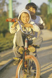 Dos muchachos de Hispanc que montan el doble en una bicicleta, CA Imagenes de archivo