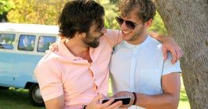 Dos muchachos de los amigos que miran en el smartphone almacen de video