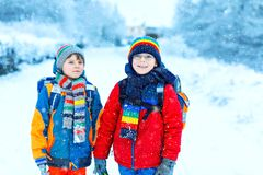 Dos muchachos de los niños de clase elemental que caminan a la escuela durante las nevadas Niños felices que se divierten y que j fotografía de archivo