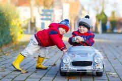 Dos muchachos de los niños que juegan con el coche del juguete, al aire libre Fotografía de archivo