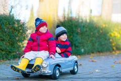 Dos muchachos de los niños que juegan con el coche del juguete, al aire libre Imagenes de archivo
