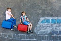 Dos muchachos de los niños que se divierten con el dibujo de la imagen del tren con tizas coloridas en el asfalto Niños que se di fotografía de archivo libre de regalías