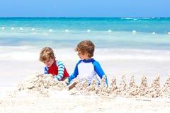Dos muchachos de los niños que se divierten con la construcción de un castillo de la arena en la playa tropical del Playa del Car imagenes de archivo