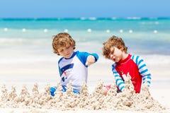 Dos muchachos de los niños que se divierten con la construcción de un castillo de la arena en la playa tropical de la isla carrib foto de archivo libre de regalías