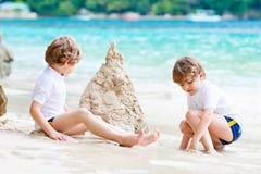 Dos muchachos de los niños que se divierten con la construcción de un castillo de la arena en la playa tropical de Seychelles Niñ foto de archivo