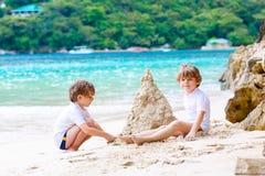 Dos muchachos de los niños que se divierten con la construcción de un castillo de la arena en la playa tropical de Seychelles Niñ fotos de archivo
