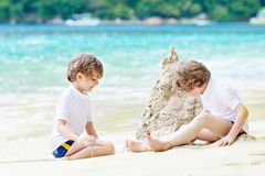 Dos muchachos de los niños que se divierten con la construcción de un castillo de la arena en la playa tropical de Seychelles Niñ fotografía de archivo libre de regalías