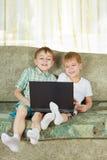 Dos muchachos de risa con el cuaderno Foto de archivo libre de regalías