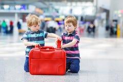 Dos muchachos del hermano que van el vacaciones disparan en el aeropuerto Fotos de archivo libres de regalías