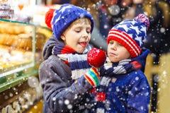 Dos muchachos del niño que comen los dulces de la manzana del azúcar se colocan en mercado de la Navidad Fotografía de archivo