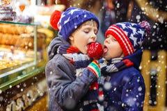 Dos muchachos del niño que comen los dulces de la manzana del azúcar se colocan en mercado de la Navidad Imágenes de archivo libres de regalías