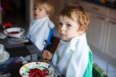 Dos muchachos del pequeño hermano que comen la avena y bayas para el desayuno Imágenes de archivo libres de regalías