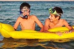 Dos muchachos disfrutan de su tiempo en la playa Imagen de archivo libre de regalías
