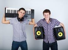 Dos muchachos divertidos con los altavoces y el piano Foto de archivo libre de regalías
