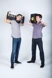 Dos muchachos divertidos con los altavoces y el piano Imagenes de archivo