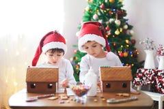 Dos muchachos dulces, hermanos, haciendo la casa de las galletas del pan de jengibre Foto de archivo libre de regalías