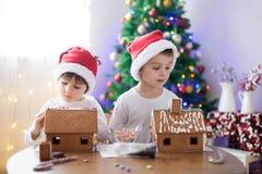 Dos muchachos dulces, hermanos, haciendo la casa de las galletas del pan de jengibre Fotografía de archivo