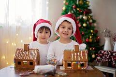 Dos muchachos dulces, hermanos, haciendo la casa de las galletas del pan de jengibre Foto de archivo
