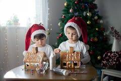 Dos muchachos dulces, hermanos, haciendo la casa de las galletas del pan de jengibre, deco Imagen de archivo libre de regalías