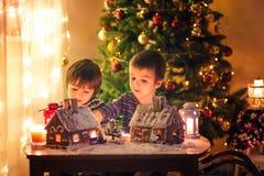Dos muchachos dulces, hermanos, haciendo la casa de las galletas del pan de jengibre, deco Fotografía de archivo libre de regalías