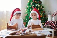 Dos muchachos dulces, hermanos, haciendo la casa de las galletas del pan de jengibre Fotografía de archivo libre de regalías