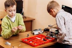 Dos muchachos elegantes están haciendo los robots del constructor robótico en el escritorio con el ordenador en la escuela de l imagen de archivo