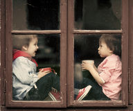 Dos muchachos en el té de la ventana, de la risa y de la consumición Fotografía de archivo