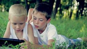 Dos muchachos en la ropa blanca ponen en la hierba en almacen de metraje de vídeo